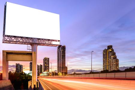 Panneau blanc sur l'autoroute au crépuscule pour la publicité.