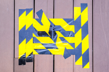 caution tape: Yellow and black caution tape marked on broken wooden floor. Stock Photo