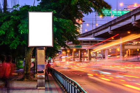 Blank advertising panel near road at night.