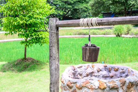 draw well: Vintage draw well with wooden drive shaft bucket. Stock Photo