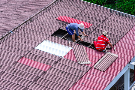 Man workers replacing damaged old tiles roof. Stock Photo