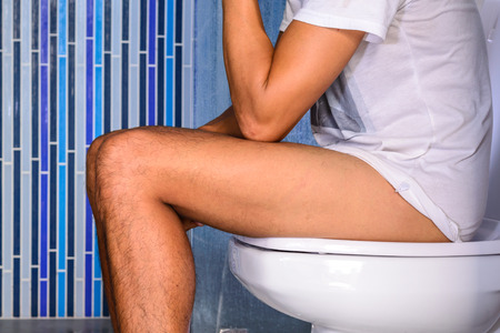 defecation: Close up of man defecating in private toilet.