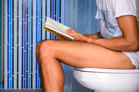 defecating: Close up of man reading a book while defecating in private toilet. Stock Photo