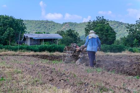 empleadas domesticas: Granjero tailandés usando tractores para caminar por terreno cultivado por preparar plantación.