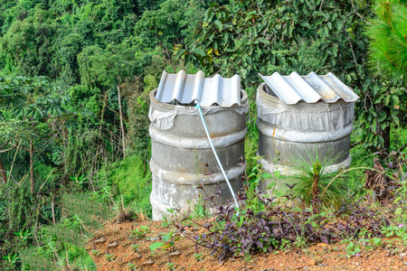 cataract: Water tank for plumbing system from cataract in forest. Stock Photo