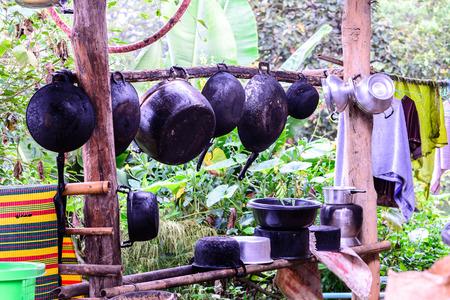 sooty: Sooty pots and pan hang on wooden bar at countryside.
