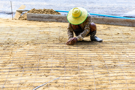 on rebar: Engineer meshing rebar for flooring with cement.