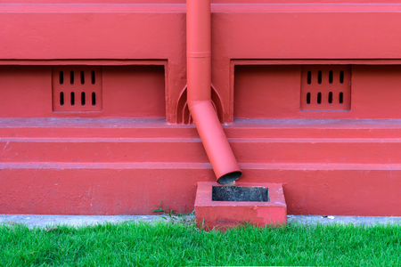 roofing system: Metal drainpipe in red color.