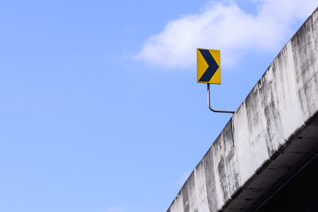 colum: Bridge and right arrow sign with blue sky.