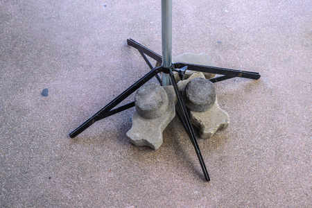 bracing: Brick block ballast on umbrella leg for stability. Stock Photo