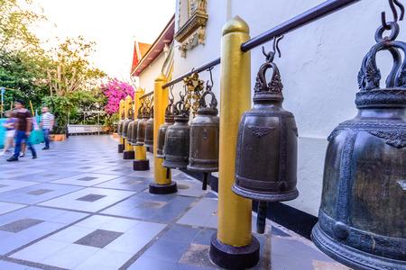 pinchbeck: Brass bells hanging under metal bar at temple.