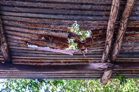 damaged roof: Damaged weathered rusty roof. Stock Photo