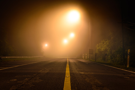 Country road with night light among the mist.