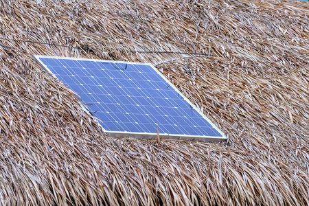 photocell: Solar cell on thatched roof for energy in forest. Stock Photo