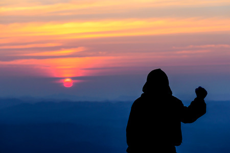 anorak: Silhouette of man in anorak standing with sunset on mountain,  success motivation concept.