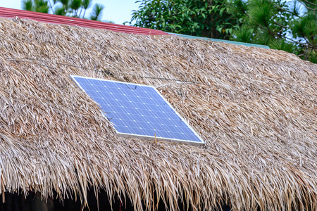thatched: Solar cell on thatched roof for energy in forest. Stock Photo