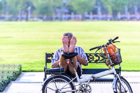 off road biking: Man relaxing with bicycle in urban park.