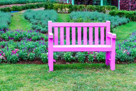 Pink wooden bench among the flower garden.