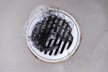clump: Hair clump in bath drain while taking a shower. Stock Photo
