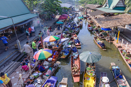 tha: SAMUT SONGKHRAM, THAILAND - 2015 December 27: Unidentified tourists and merchants on vintage boats at Tha Kha Floating Market in Samut Songkhram, Thailand.