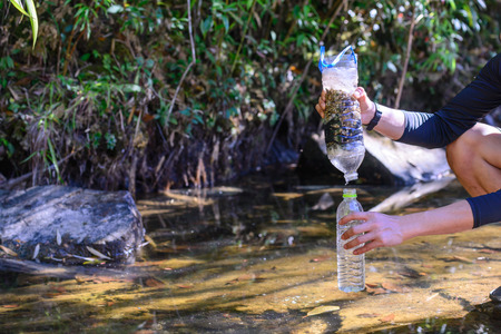 Simple natural water filtering gear use for outdoor camping. Foto de archivo