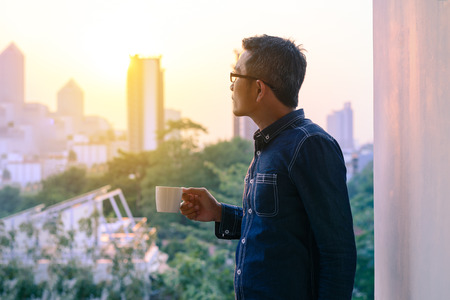 Businessman in denim jacket and glasses drinking hot coffee in sunrise.