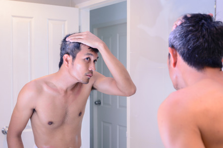 calvo: El hombre preocupado por el pelo gris mientras se mira en un espejo.