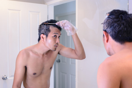Hair coloring gray hair, man make a coloring with mirror by oneself. Stock Photo