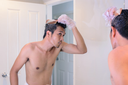 oneself: Hair coloring gray hair, man make a coloring with mirror by oneself. Stock Photo