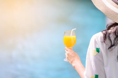 verre de jus d orange: Vue arrière de la belle femme au chapeau tient orange, verre de jus au bord de la piscine en été. Banque d'images