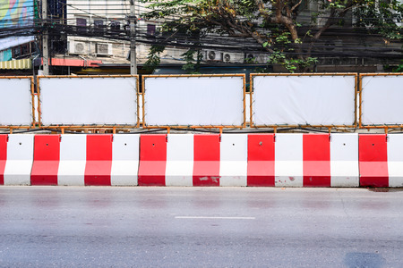 roadwork: Red and white concrete barrier at roadwork construction. Stock Photo