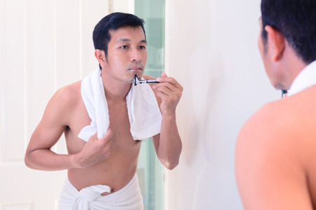 oneself: Young handsome man shaving by oneself with mirror.