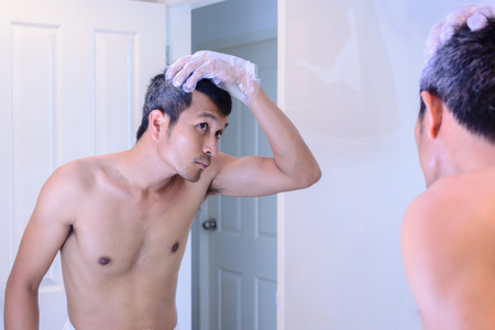 beautycare: Man worried about gray hair while looking into a mirror.