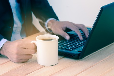 mug of coffee: Businessman  holding coffee cup and typing a laptop on wooden table.
