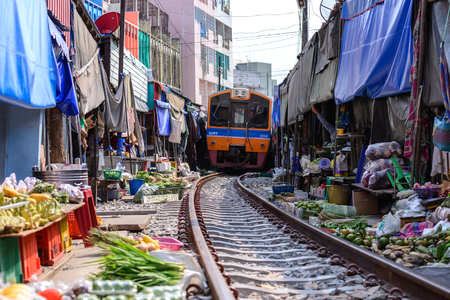 SAMUT SONGKHRAM, THAILAND - 2016 MAY 08: Mae Klong Market placed all product on railroad, all vendors have to move product away when the train passes market. Banco de Imagens - 58566130