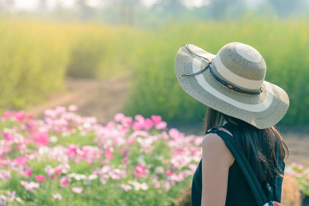 Beautiful woman in straw hat standing near colorful flowers.