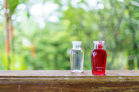 Red shampoo bottle place on table with nature background.