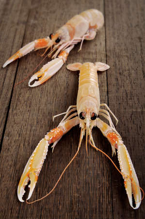 scampi: Couple of fresh shrimp scampi on a wooden cutting board