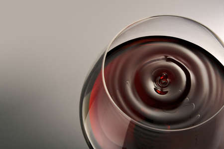 redness: Droplet of red wine falling in a glass