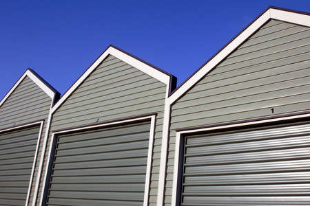 A row of uniform garages with roller doors on a blue sky background  Stock Photo