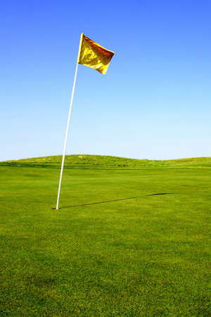 A pristine golf green and flag in the morning. Banco de Imagens