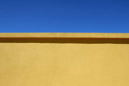 A rendered concrete wall and a blue sky.
