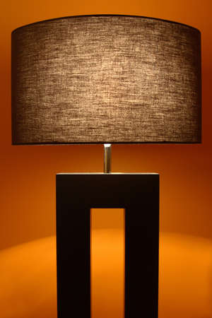 A contemporary black lamp on a rustic background.