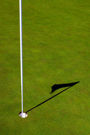 A pristine grass golf green hole and shadow of the pin. Stock Photo
