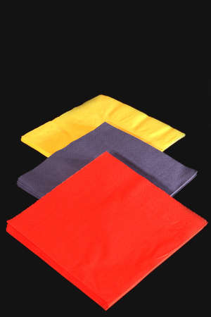 Three stacks of colored napkins on a black background.