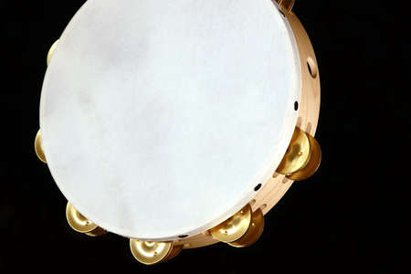 A tambourine close up on a black background.
