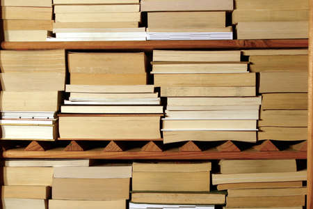 Stacks of books on a wooden shelf. Stock Photo