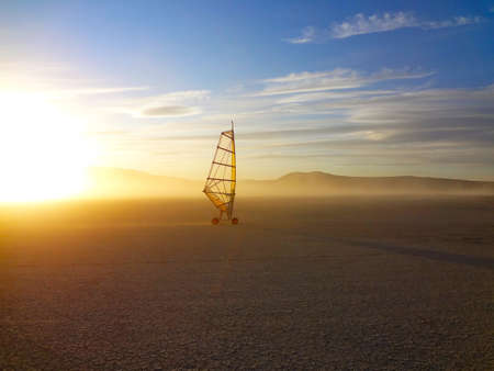 A single land wind surfer on a remote dry lake bed.