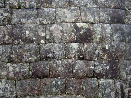An ancient stone wall background with weathered texture.                             Stock Photo