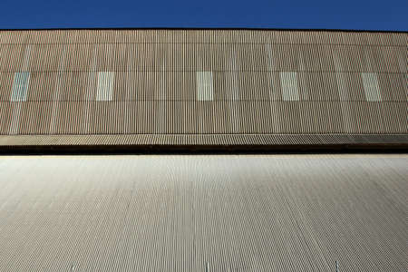A large corrugated iron shed structure with clear blue sky.